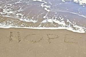 HOPE written in sand in front of surf - graphic stock